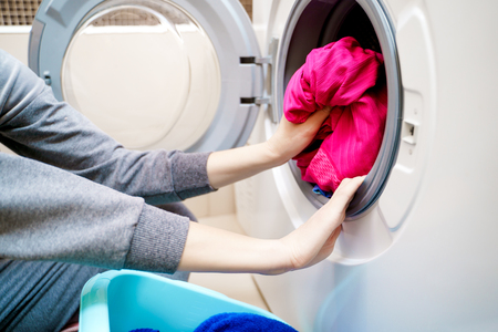 Photo of woman hands putting dirty clothes in washing machine .