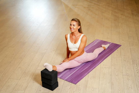Young woman doing splits on mat .
