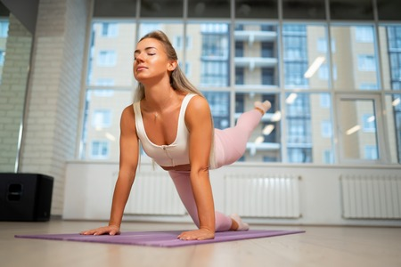 Young athlete woman standing on all fours on mat doing yoga.
