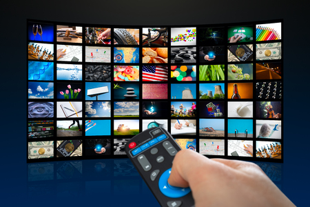 TV screen with lot of pictures and hands of man with remote control on blue background Imagens