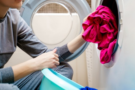 Photo of woman hands putting dirty pink clothes in washing machine. Stock Photo