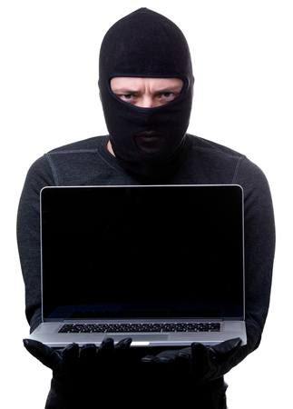 Thief in black mask with laptop in hand. Stock Photo