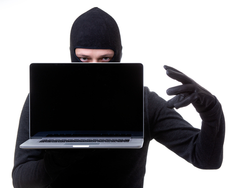 Hacker in black mask with laptop with blank screen in hands. Stock Photo