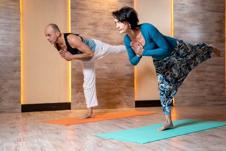 Man and woman are practicing yoga while standing on one leg on blue mat. Imagens