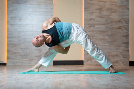 Sportive man looking up with raised arm doing yoga on blue mat in gym.