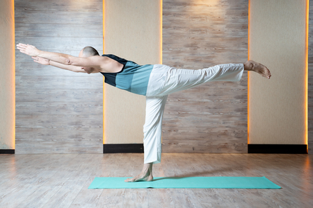 Athletic man standing on leg with arms stretched forward doing yoga on blue mat . Imagens
