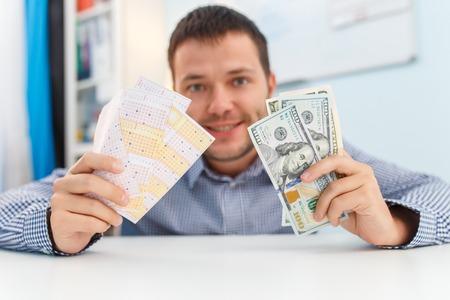 Foto de hombre feliz con billete de lotería y dólares. Foto de archivo