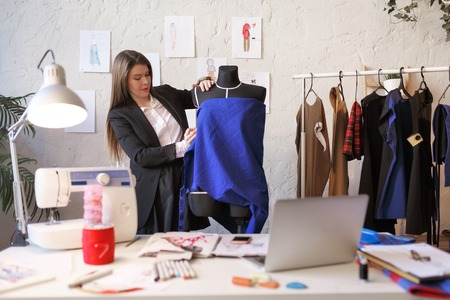 Photo of long-haired seamstress woman standing next to mannequin with blue cloth. Stockfoto