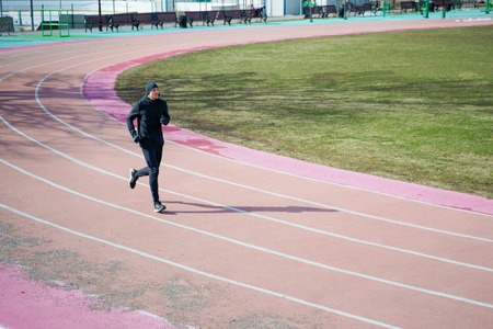 Photo of athlete man running through stadium during spring jog. Reklamní fotografie