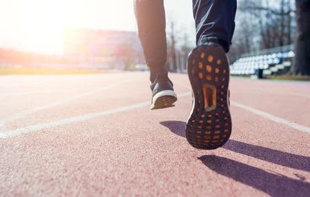 Zdjęcie z tyłu nóg sportowca biegnącego przez stadion