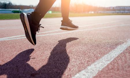 Photo from side close-up of athletes feet running around stadium Imagens