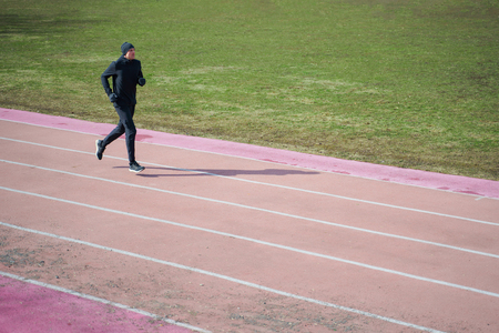 Photo of sports male running through stadium during spring jog