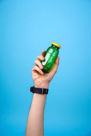 hand holding glass bottle on blue background