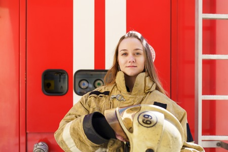 Photo of fire girl standing at fire truck Фото со стока