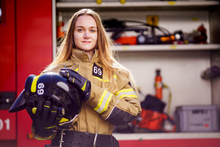 Photo of woman firefighter with helmet in her hands standing near fire truck