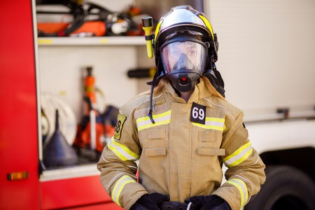 Image of woman firefighter in helmet and mask standing near fire truck