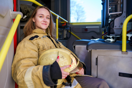 Image of woman firefighter with helmet in hands sitting in fire truck Stock Photo