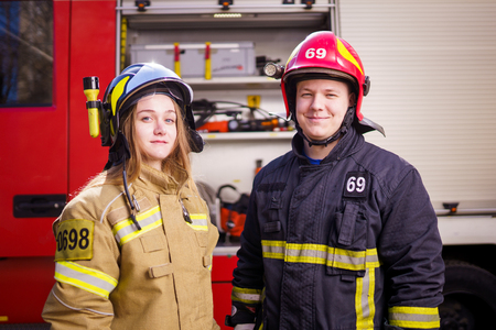 Photo of firefighters women and men in helmets looking at camera near fire truck Stock Photo