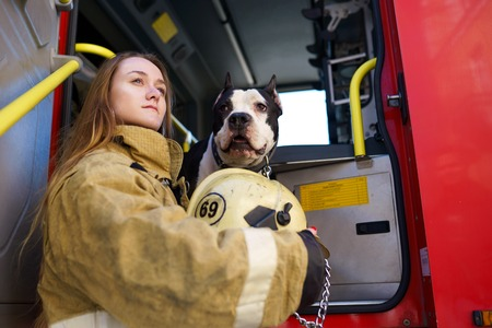 Image of firewoman with dog standing near fire truck