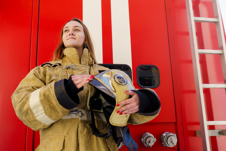 Image of girl fire looking on side of standing at fire truck at station