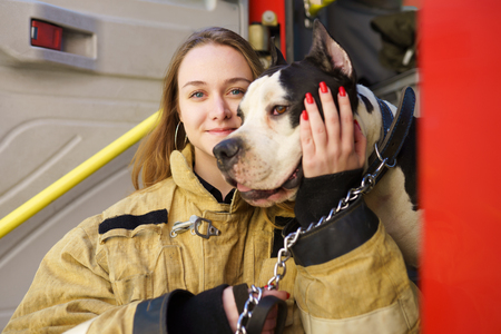 Image of happy firewoman with dog standing near fire truck Stock Photo