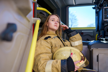 Photo of woman firefighter with helmet in hands sitting in fire truck Stock Photo