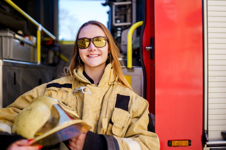 Image of smiling fire woman in glasses with helmet in hands sitting in fire truck Stock Photo