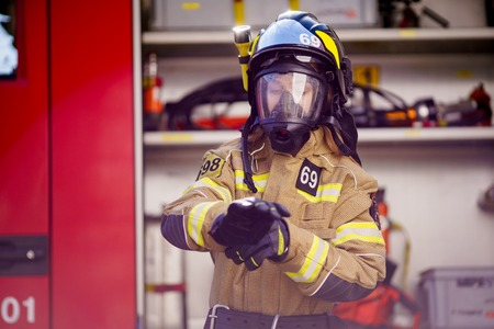 Photo of woman firefighter in helmet and mask standing near fire truck Stock Photo