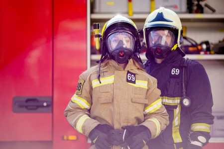 Photo of woman and man firefighters in helmet and mask next to fire truck Standard-Bild
