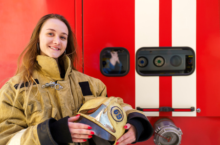 Photo of fire blonde woman standing at fire truck