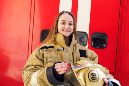 Photo of happy fire girl standing at fire truck