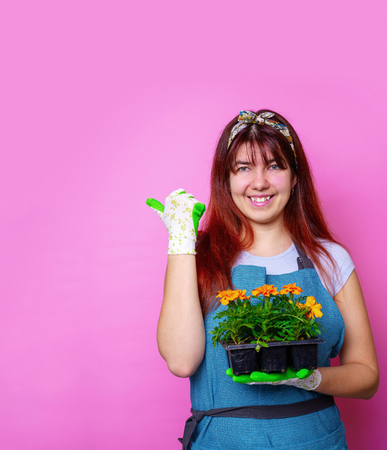 Photo of happy girl with marigolds , pointing to side