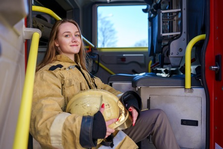 Photo of happy fire woman standing at fire truck