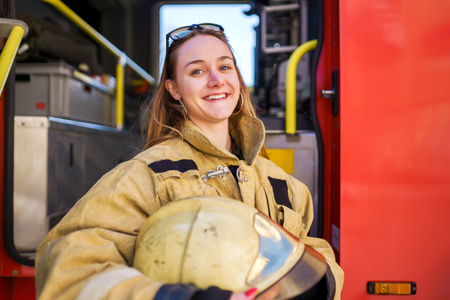 Photo of smiling woman firefighter with glasses on head standing next to fire truck at fire station