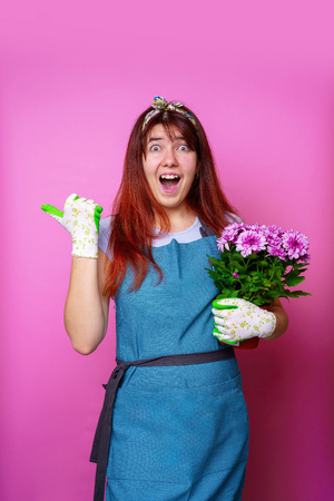 Photo of happy girl with chrysanthemum pointing hand to side