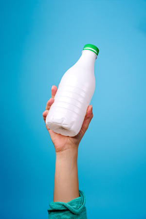 Plastic bottle in hand against blue background.