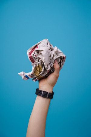 hand with crumpled newspaper.