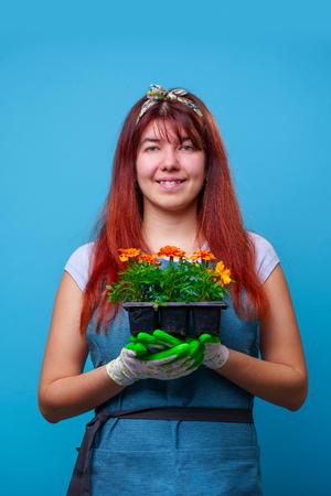 Image of happy brunette with marigolds in her hands
