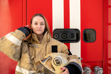 Photo of young fire girl standing near fire truck