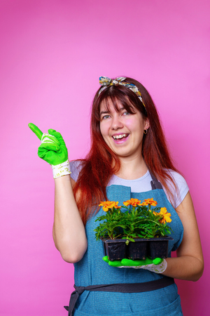 Photo of happy brunette with marigolds , pointing to side