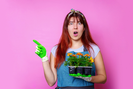 Image of surprised woman with marigolds pointing hand to side