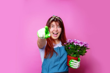 Photo of cheerful girl with chrysanthemum pointing hand to forward