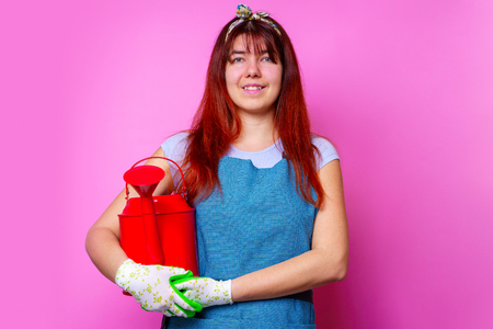 Image of happy florist brunette woman with watering can in hand