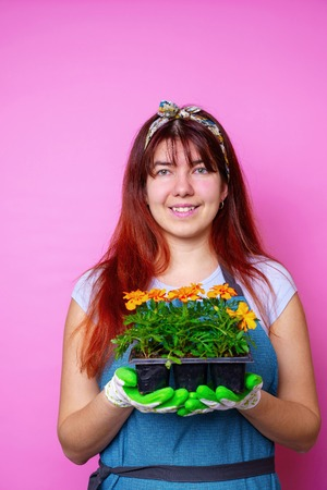 Photo of happy woman with marigolds in her hands