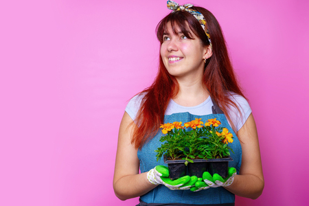 Photo of happy woman looking at side with marigolds in her hands