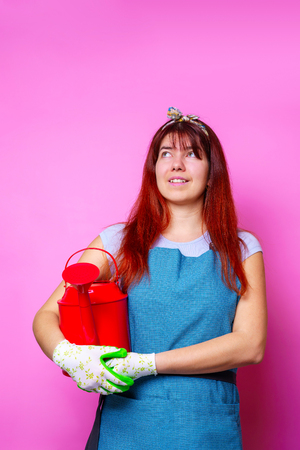 Photo of happy florist brunette woman looking up with watering can in hand