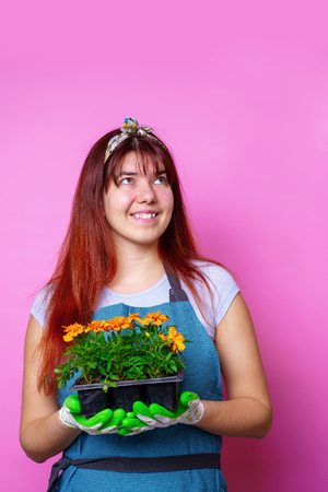 Image of happy woman looking at side with marigolds in her hands