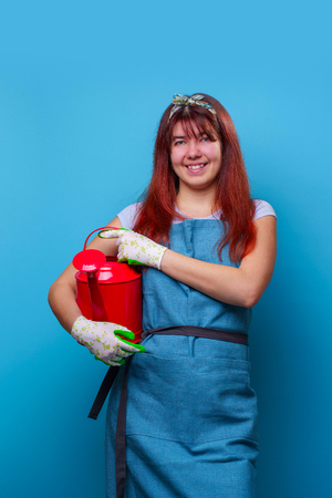 Photo of smiling girl florist with watering can in hands of pointing finger to side Stock Photo