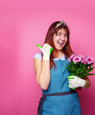 Image of cheerful woman with chrysanthemum pointing hand to side Stock Photo