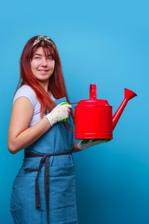 Photo of cheerful florist brunette woman with watering can in hand